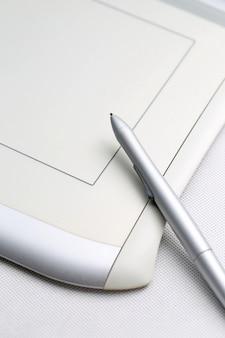 Графический планшет и ручка, чувствительная к давлению на белом фоне