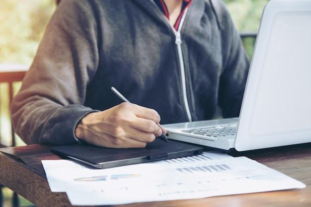 Азия среднего возраста внештатный, работающий с ручкой мыши на ноутбуке