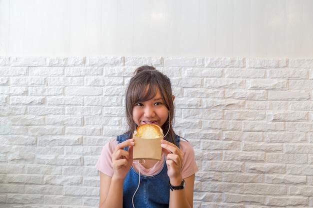 チーズのパン焼きを食べる少女。