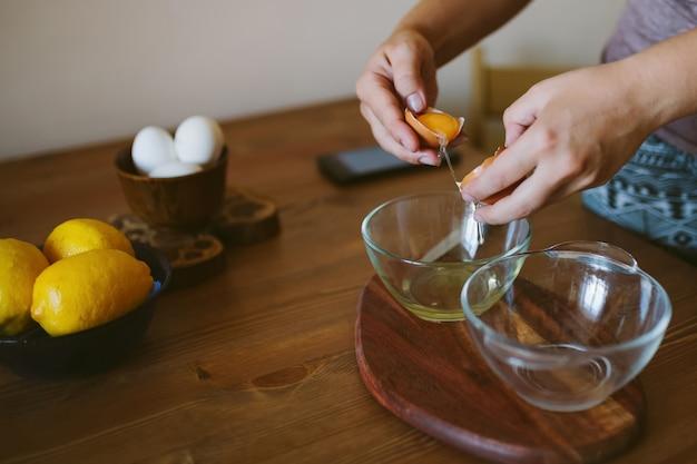 卵をボウルに割る女性の手。