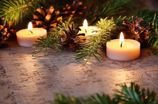 Горящие рождественские свечи украшенные еловыми ветками