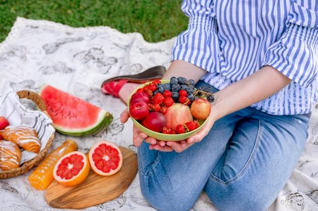若い女性は、ピクニックにフルーツボウルを保持しています。