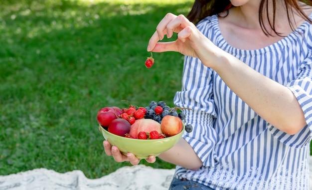 Молодая женщина держит вазу с фруктами на пикник.