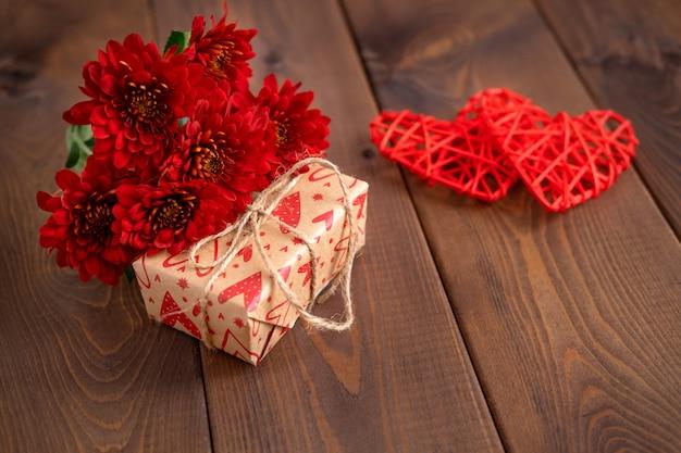 Красные цветы и сердца на деревянной доске. день святого валентина фон. день святого валентина карты с копией пространства для текста.