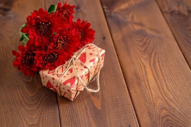 Красные цветы и ремесло подарок на деревянной доске. день святого валентина фон. концепция карты святого валентина