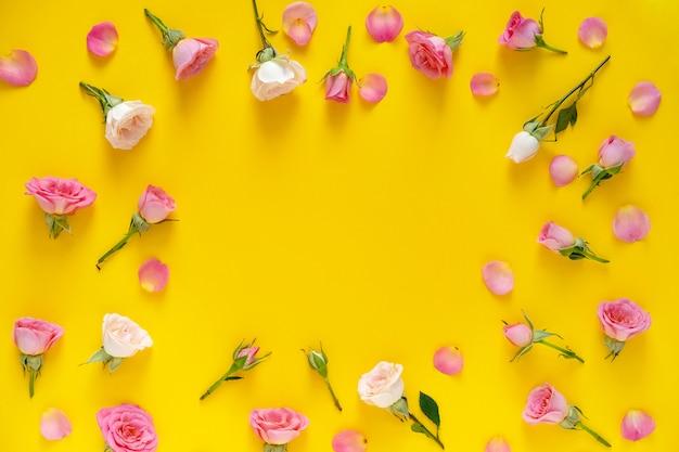 バレンタインデーの背景。ピンクとベージュのバラで作られたラウンドフレーム花柄、黄色の背景に緑の葉。