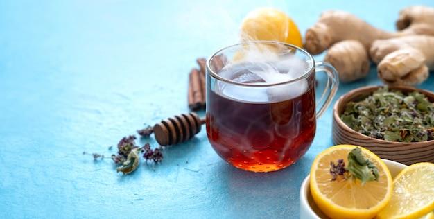 青い表面にガラスのコップにレモンとジンジャーティー