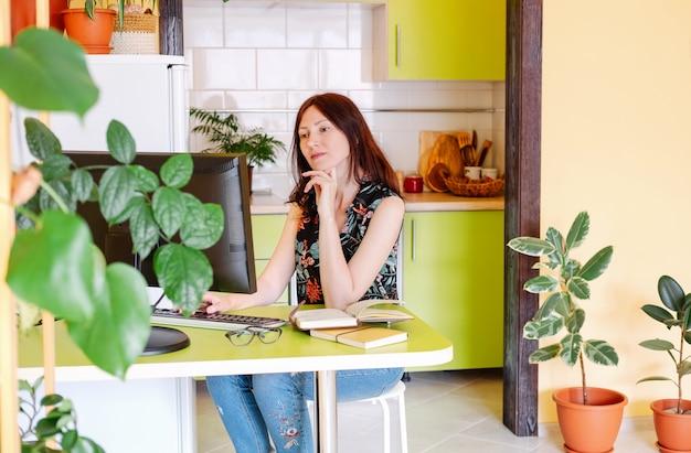 Портрет молодой красивой женщины, работающей с компьютерами дома или на рабочем месте