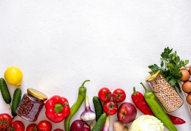 Стеклянные банки с нутом и фасолью и экологически чистыми овощами и фруктами
