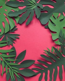 紙の花と葉で作られた創造的な装飾的な花のフレームを手作りし、青にさまざまな葉を持つ招待状のカード。平干し。