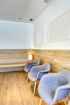 灰色の椅子、写真、白い壁を備えたモダンなデザインのレセプション。木製の床とスクリーン。歯科医院。