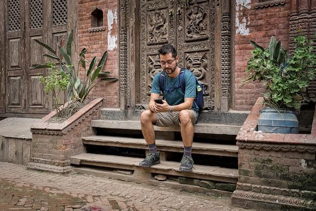 ネパールの彫刻が施された木製のドアの隣の通りに座っているショートパンツを持つ日本人観光客は、スマートフォンをチェックしています