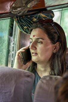電話で話している地元のカトマンズのバスの額(ビンディ)に赤い点のインドゥを持つ西洋の女性観光客