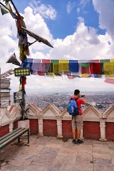 猿の寺院からネパールのカトマンズの街の写真を撮る旅行者。彼は赤いシャツ、ショートパンツ、小さな青いバックパックを着ています。色付きのチベットの祈りの光と旗があります