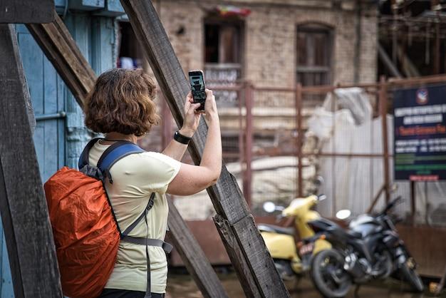 アジアのネパールのヒンズー教の寺院を彼女のスマートフォンで撮影する短いブルネットの髪を持つ若い女性。防水カバー付きオレンジバックパック