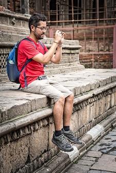 メガネ、ひげ、ネパール、アジアのヒンズー教の寺院で宙に浮いた足で座っている彼のスマートフォンで撮影短いブルネットの髪を着ている少年。小さな青いバックパック旅行