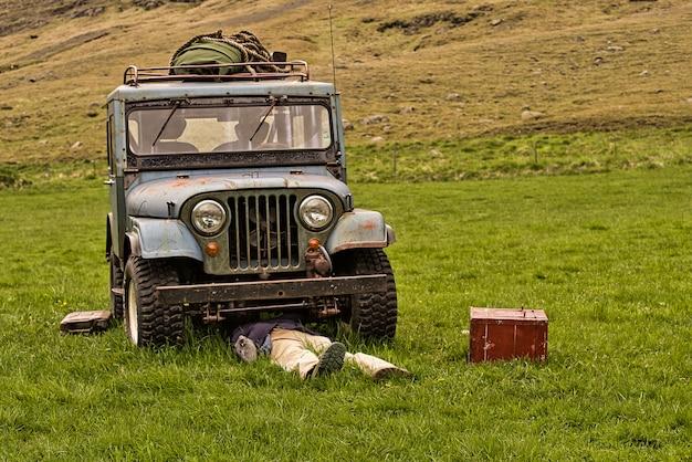 緑の牧草地に置かれた壊れた古い老朽化したオフロード車の下のメカニックまたはドライバー。メタリックレッドのツールボックス。