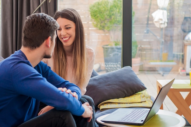 恋人の女性奇妙な彼女の男の話を聞いて、幸せなカップルお互いを見て笑顔、ロマンチックなカップルは自宅でリラックス