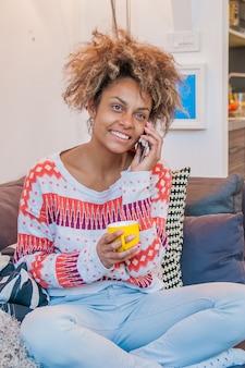 Живая красивая молодая афро-американец с афро-прической, болтая на своем мобильном телефоне, слушая звонок с широкой сияющей улыбкой восторга
