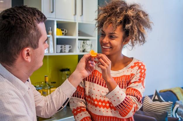 健康的な食べ物を食べる若いカップル。幸せなカップルは、新鮮な果物を食べています。キッチンで楽しく過ごしましょう。ディーリングコンセプト。健康的な食事