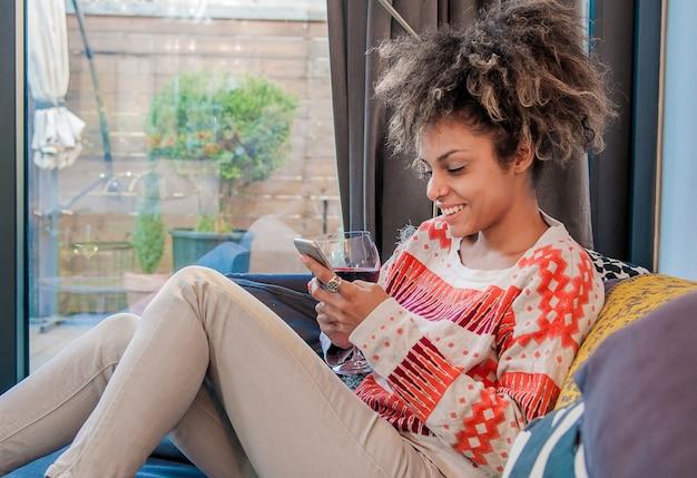ソファに座ってテキストメッセージを読むアフリカ系アメリカ人女性を笑って。若い女性は自宅で笑いを浮かべて笑顔で、彼女はスマートフォンと文字通り、技術とコミュニケーションのコンセプトを使用しています