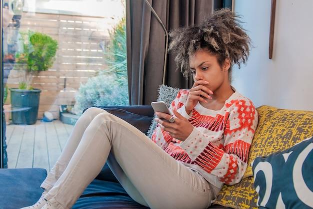 若い女性が電話で悪いニュースを受け取ります。不幸な若い女性が携帯電話で話をしている。人間の顔の表情、感情、悪いニュースの反応