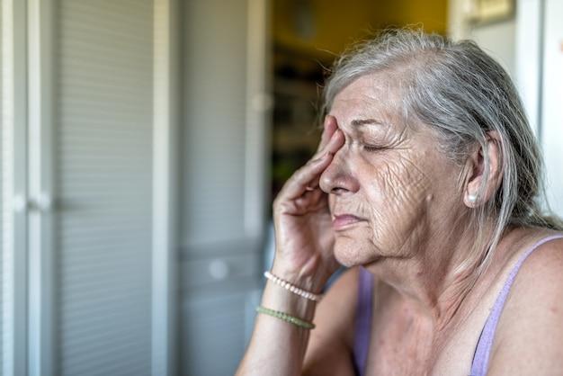 悲しい落ち込んだ、ストレス、思いやりのある、シニア、老いた女性、暗い、心配、彼女の顔を覆う