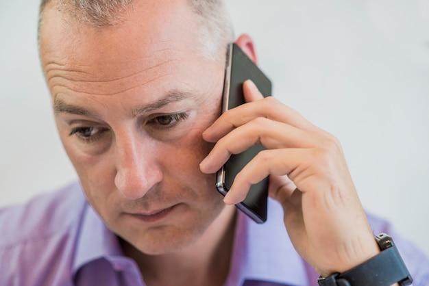 Портрет взволнованный зрелый человек разговаривает с смартфоном