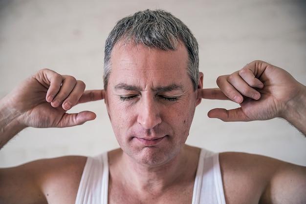 肖像画が成熟し、耳を覆う、不快でストレスの多い男。否定的な感情反応。その大きな騒音を止める。顔の表情これは大きすぎます!彼の耳に指を置き、目を閉じたままにしておく、懐疑的な成熟した男
