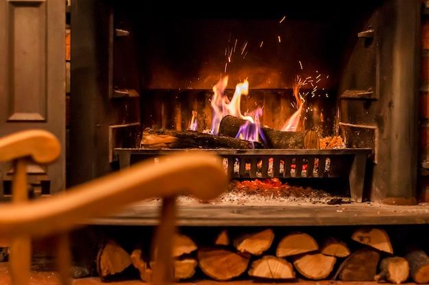 家の快適さ。暖炉のそばのロッキングチェア。部屋の内部の写真。モダンな暖炉が施されたリビングルームのロッキングチェア