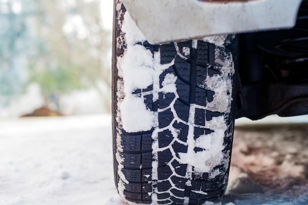 雪に覆われた冬の道にカータイヤ。降雪時の朝の雪路の車