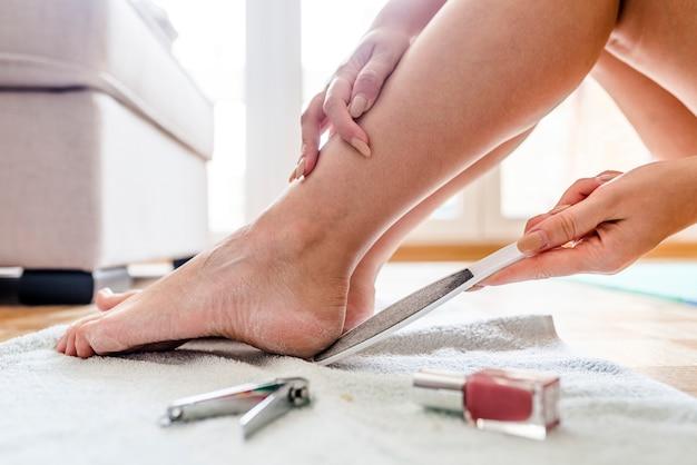 女性の足の細部のケア。彼女の足にペディキュアを持つ女性のクローズアップ