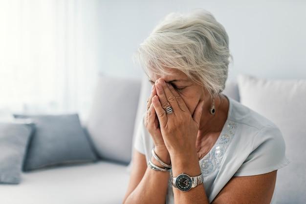 Старшая женщина, страдающая головной болью у себя дома