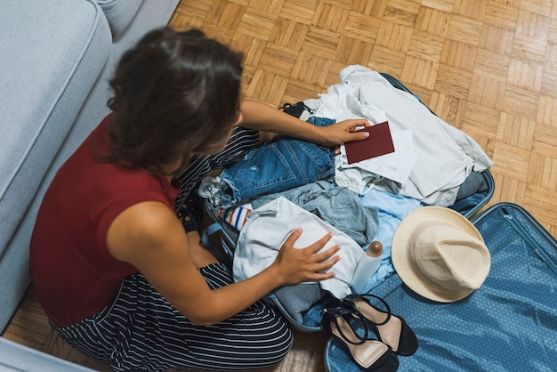Молодая девушка случайно упаковывает чемодан