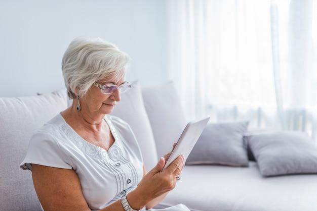 高齢者、女性、メッセージ、電子書籍、または彼女のタブレットコンピュータの情報を見て