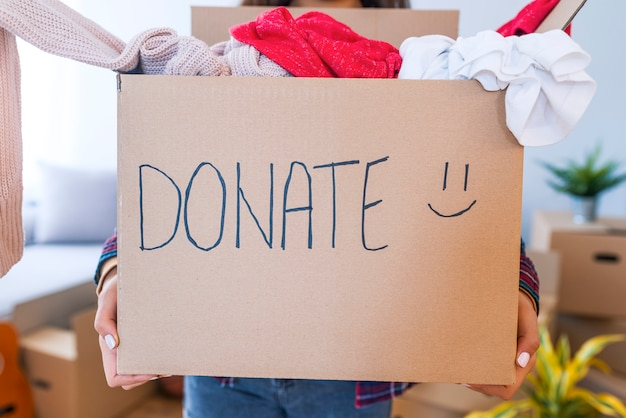 寄付のコンセプト。衣服がいっぱいの寄付箱を持っている女性