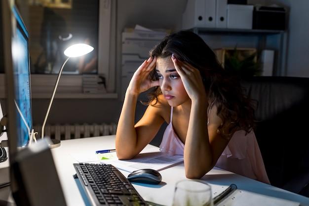 彼女のコンピュータとオフィスデスクで働く眠そうな疲れた女性、彼女の目は閉じている