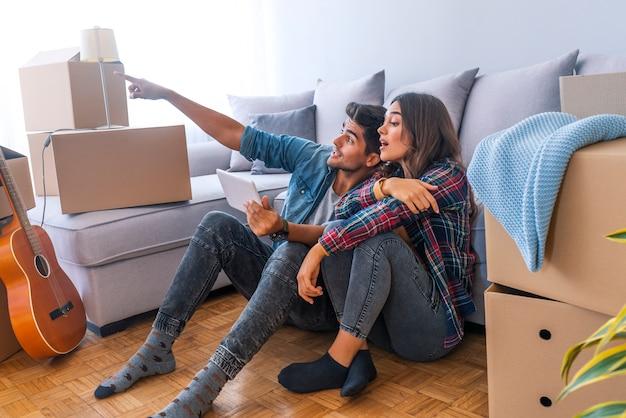 新しい家を動かすカップル。幸せな既婚者は新しいアパートを購入する