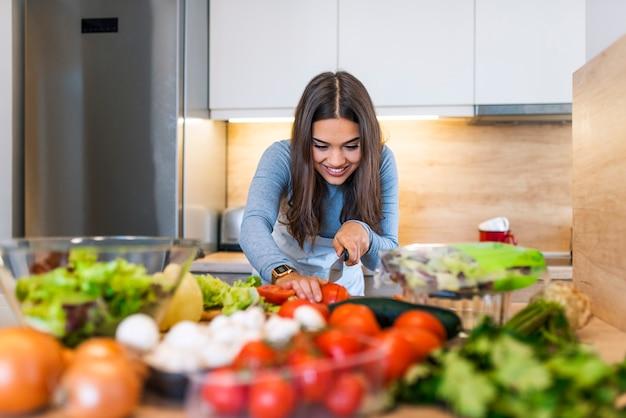 楽しくて幸せな若い女性は、台所で立って料理する。彼女は木のボアでレタスを切る