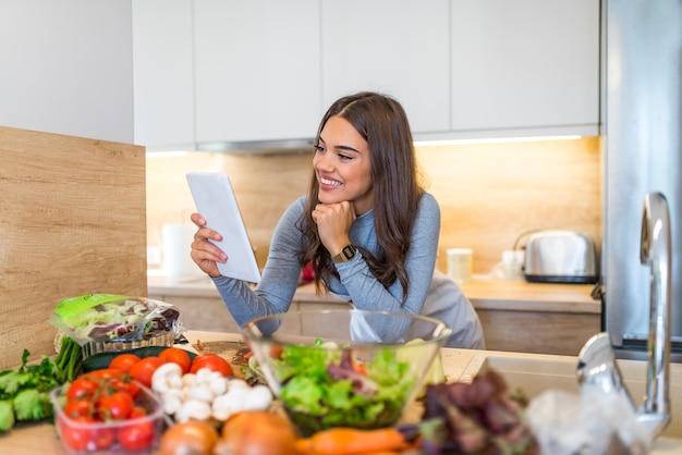 彼女の台所で料理するためにタブレットコンピュータを使用している若い女性