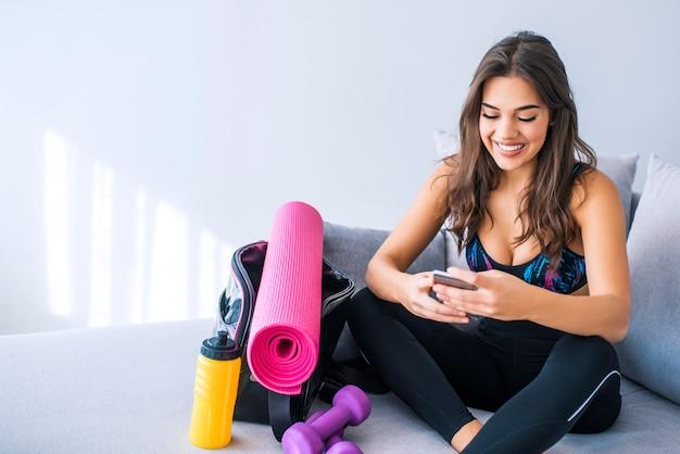 ベッドで携帯電話を使用している女性アスリート