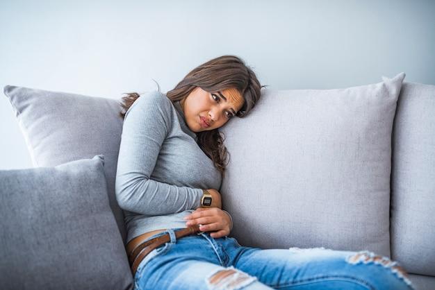 自宅のベッドに座っている間腹痛に苦しんでいる若い女性