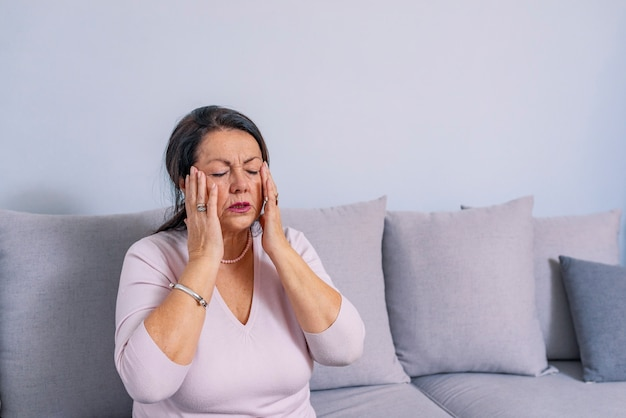 ストレスや痛みで顔をゆがめた頭痛に苦しんでいる女性