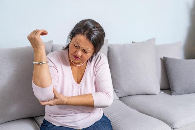年配の女性が自宅で手に痛みに苦しんでいます。