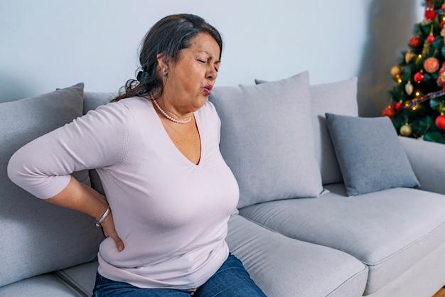 自宅で腰痛に苦しんでいる年配の女性