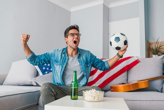 自宅でサッカーを見ている男