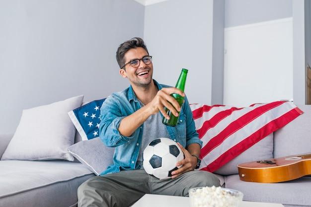 興奮して男がビールを飲みながらソファに座ってサッカーを見ています。