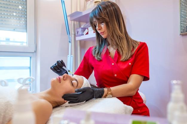 Мезотерапия на лбу. мезотерапия. процедура мезотерапии. врач косметолог проводит процедуру мезотерапии в голове женщины. укрепить волосы и их рост.