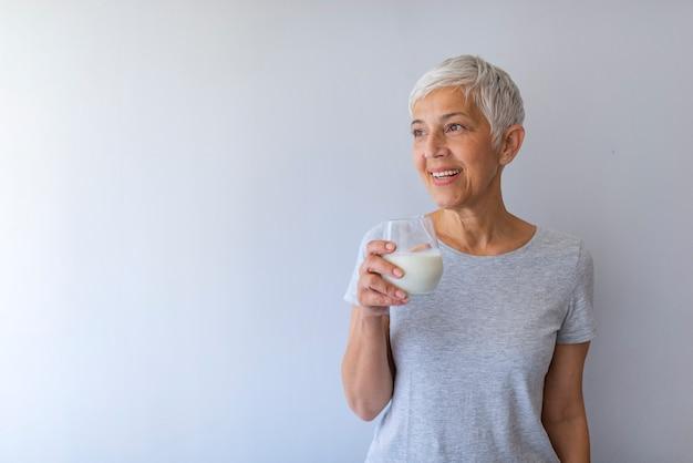 Женщина среднего возраста выпивая стекло парного молока с счастливым лицом стоя и усмехаясь с уверенно улыбкой показывая зубы.