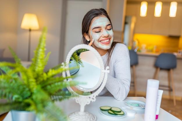 自宅の女性は顔シートマスクを適用しています。化粧品の手順、スキンケア用マスク、若い女性。顔のマスクを持つ美しい女性。